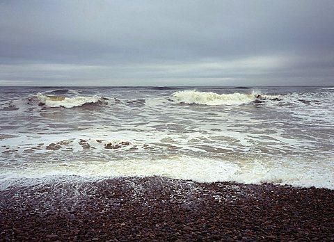 North facing shingle beach looking out across rough sea and surf, Kingston, Moray, Scotland